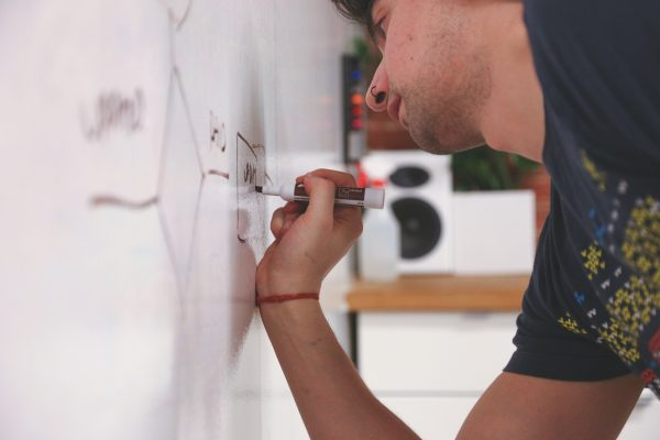 man writing diagram on whiteboard